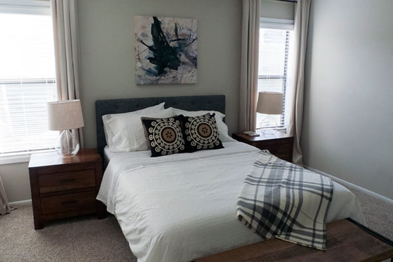 Plush carpeting and draped windows in the primary bedroom of a model home at The Everette at East Cobb in Marietta, Georgia