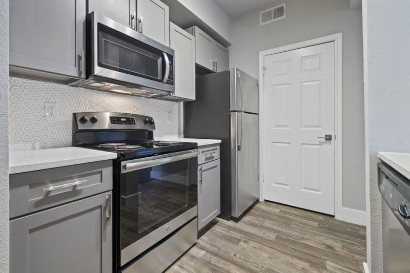 Stainless steel appliances in a model home's kitchen at Emerson at Ford Park in Allen, Texas