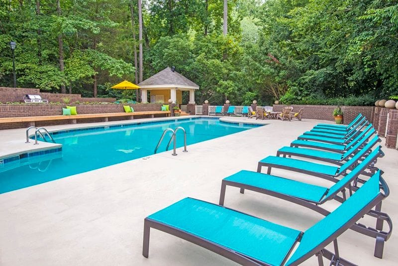 Lounge chairs beside the sparkling pool at Hamilton Ridge Apartments