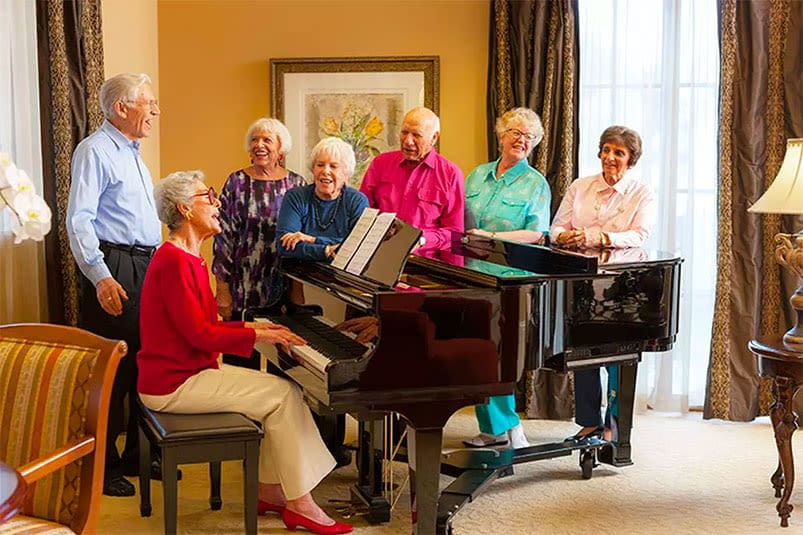 Happy seniors singing around piano at Senior living in Carlsbad CA
