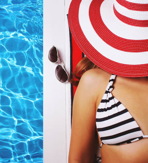 Woman in the striped bikini sporting a red and white striped hat floating in pool at Heritage Plaza in San Antonio, Texas