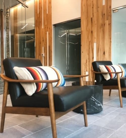 Dark wood chairs with black leather cushions and colorful accent pillows in the community space at Heritage Plaza in San Antonio, Texas