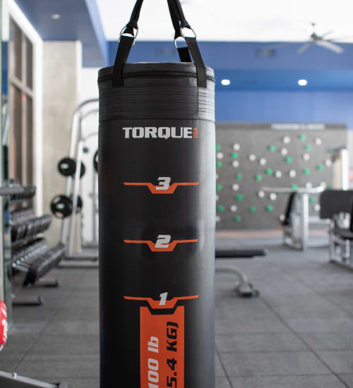 Community fitness center at Heritage Plaza in San Antonio, Texas features a Large hanging black punching bag and free weights.