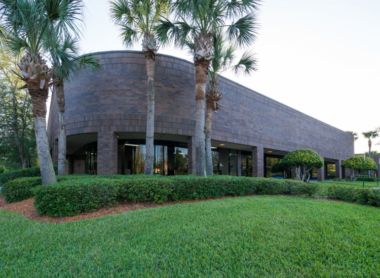 Green lawn and nicely trimmed shrubberies outside Fort Family Investments's commercial property, Interstate South Commerce Center, in Jacksonville, Florida