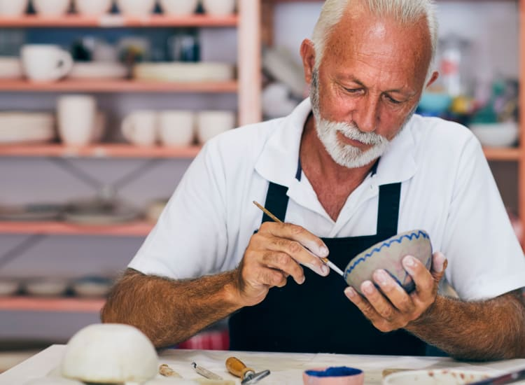 Resident working on a bowl in the pottery class at Riverwalk Pointe in Jupiter, Florida