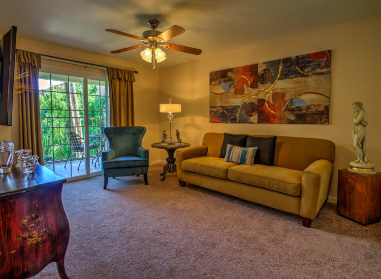 Plush carpeting and a ceiling fan in the open-concept living space of a model senior apartment at Bella Vista Senior Living in Mesa, Arizona