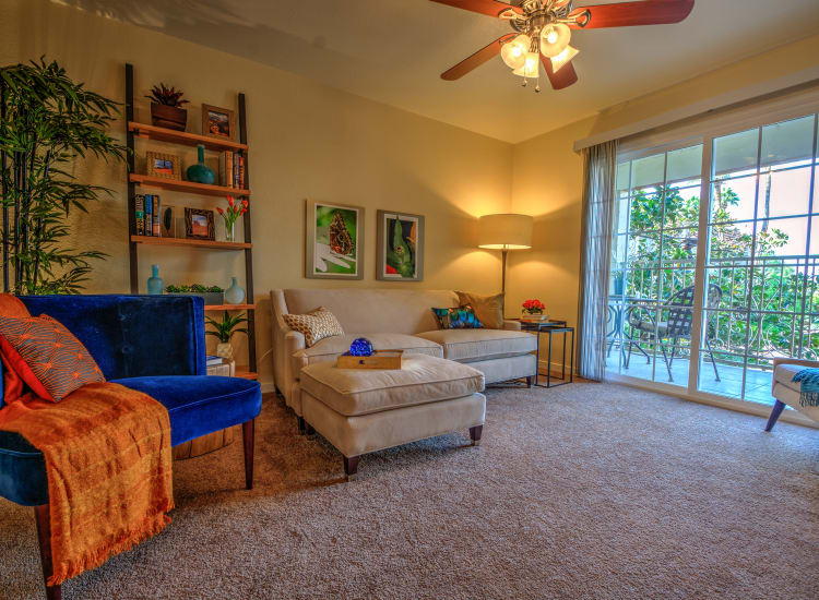 Well-decorated living area with a ceiling fan looking out onto the private balcony of a model senior apartment at Bella Vista Senior Living in Mesa, Arizona