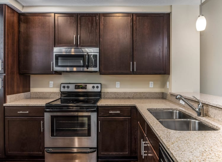 Modern kitchen with dark wood cabinetry in a model senior apartment at Riverwalk Pointe in Jupiter, Florida