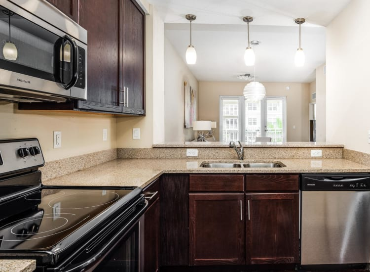 Stainless-steel appliances and granite countertops in a model senior apartment at Riverwalk Pointe in Jupiter, Florida