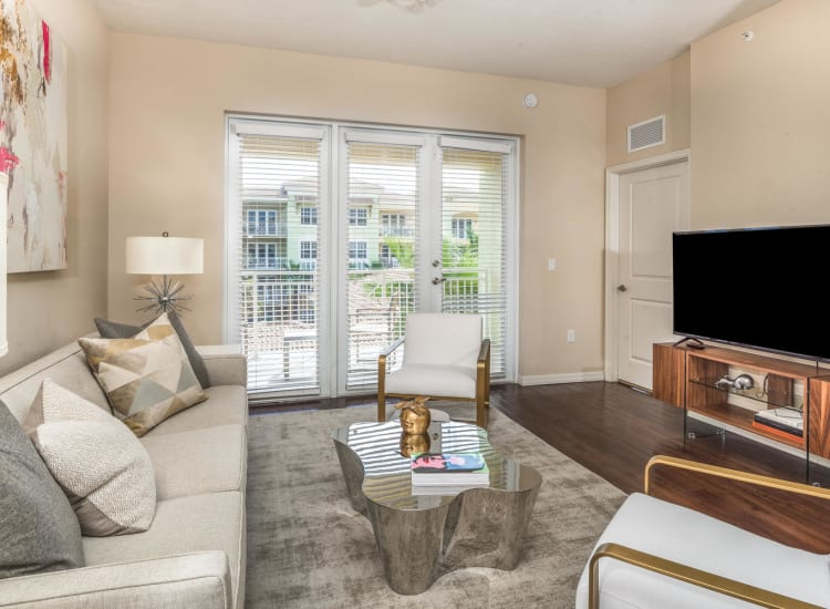 View of the private balcony through French doors from the living area in a model senior apartment at Riverwalk Pointe in Jupiter, Florida