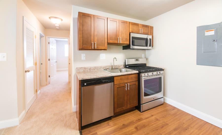 Hallway and modern kitchen in model home at Westgate Apartments & Townhomes in Manassas, Virginia