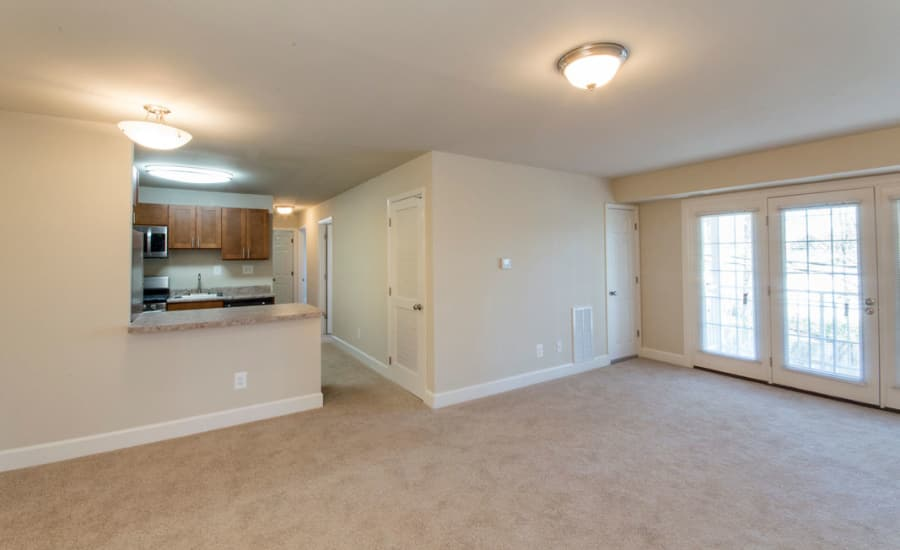 French doors and plush carpet in open-concept living area of model home at Westgate Apartments & Townhomes in Manassas, Virginia
