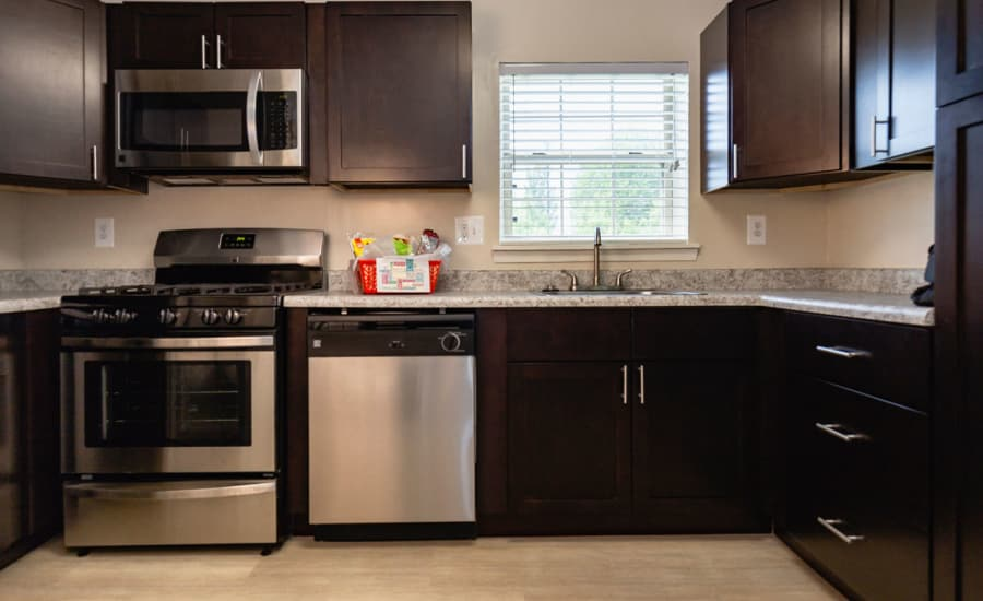 Rich, dark wood cabinetry and granite countertops in model home's kitchen at Westgate Apartments & Townhomes in Manassas, Virginia