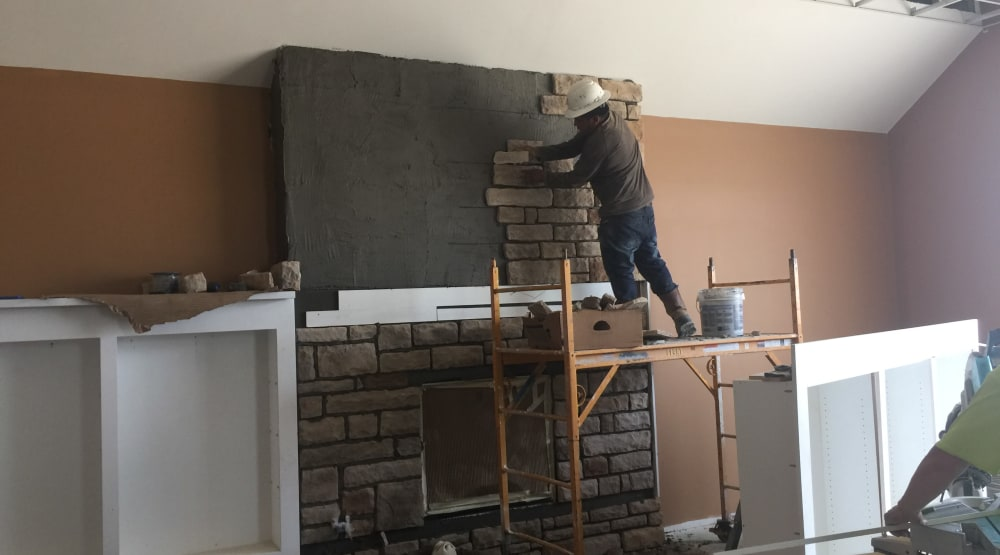 Construction worker putting in a fireplace at Randall Residence of Centerville in Centerville, Ohio