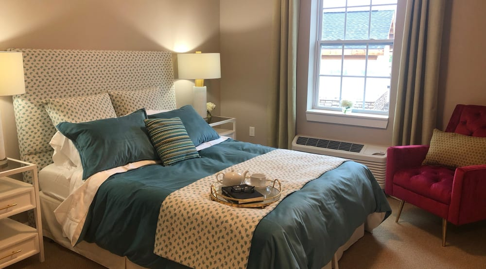 Senior apartment bedroom with air conditioning and a large bed at Randall Residence of Centerville in Centerville, Ohio