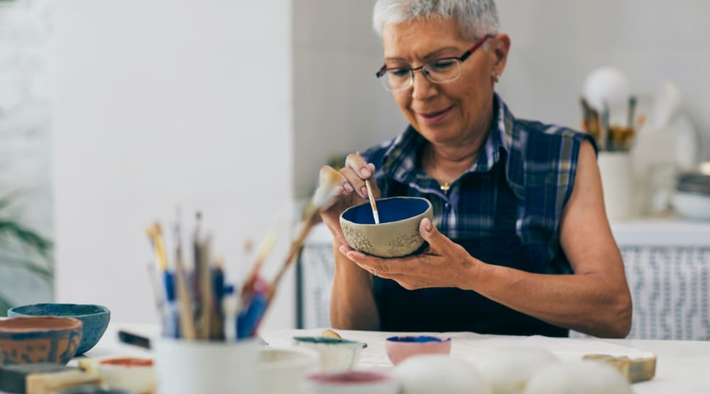 Resident painting a bowl at Randall Residence of Sterling Heights in Sterling Heights, Michigan