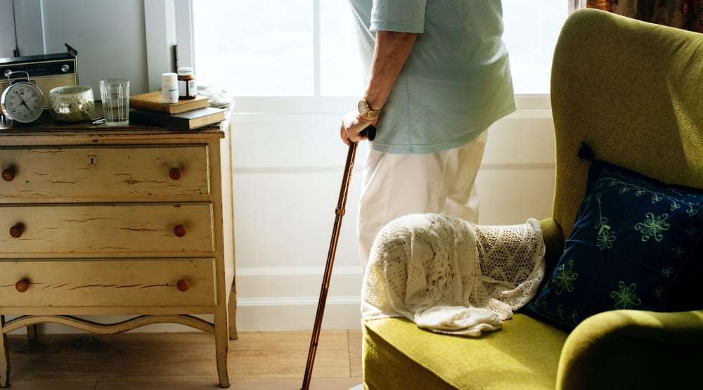 Resident with a cane walking in their apartment at Randall Residence of Sterling Heights in Sterling Heights, Michigan