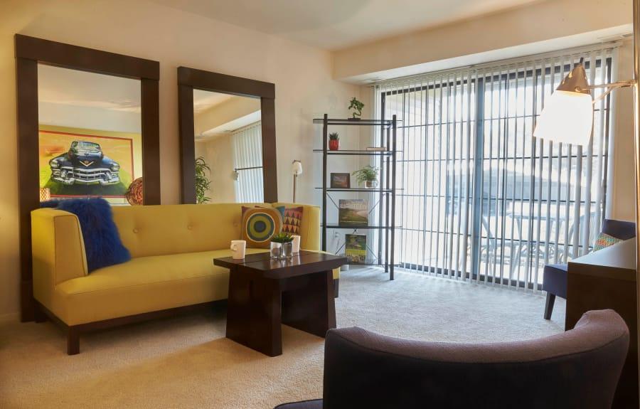 Furnished model living room with sliding glass doors at Muirwood in Farmington/Farmington Hills, Michigan