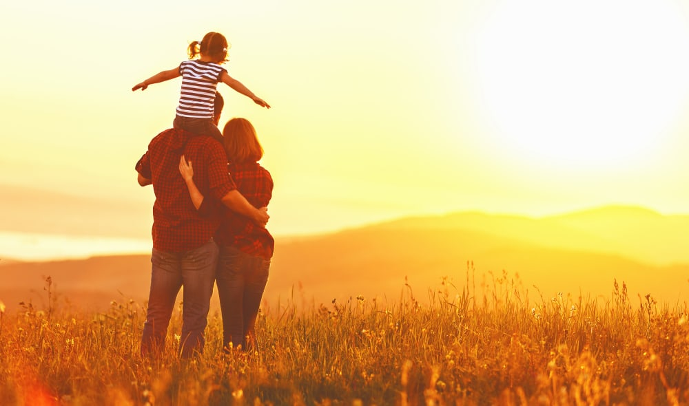 Family of three viewing the sunset at Timnath Trail at Riverbend Apartment Homes in Timnath, Colorado