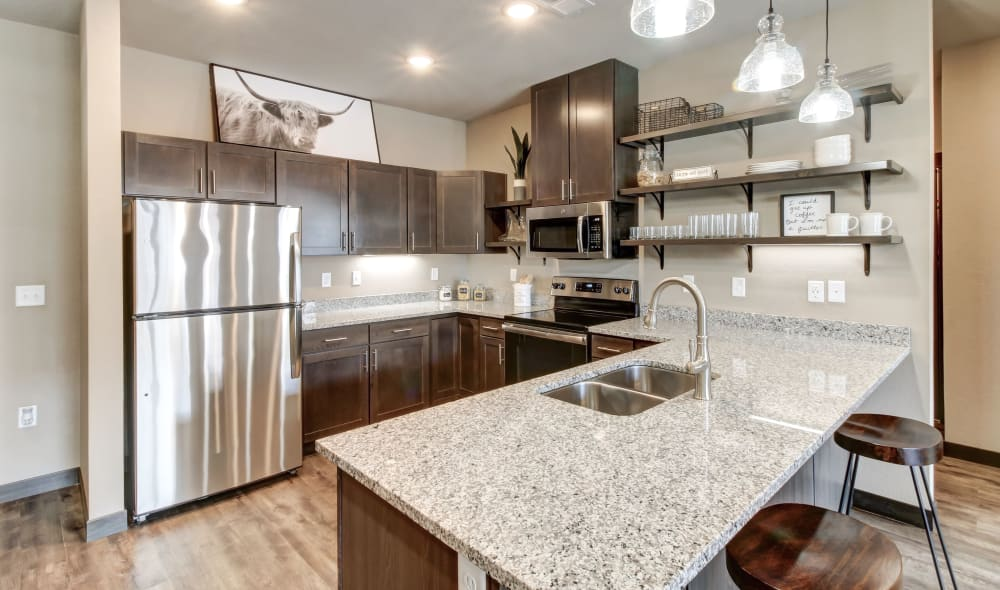 Kitchen at Timnath Trail featuring granite counters, stainless steel appliances, and open shelving