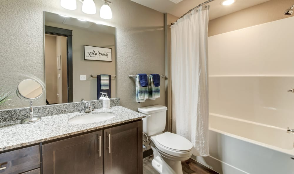 Spacious Timnath Trail bathroom with real wood cabinets and granite counters
