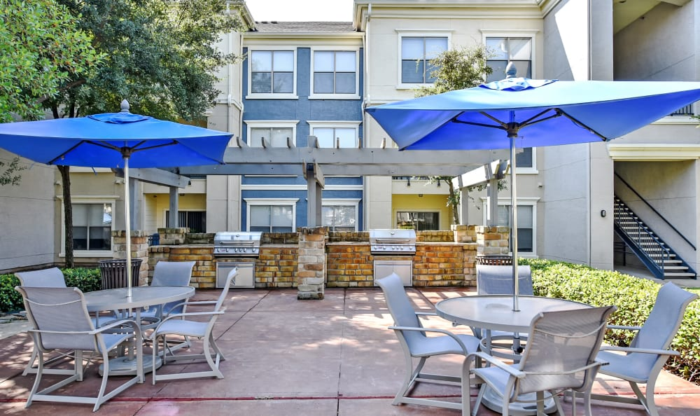 Shaded outdoor seating near the grilling area at Abbey at Vista Ridge Apartments