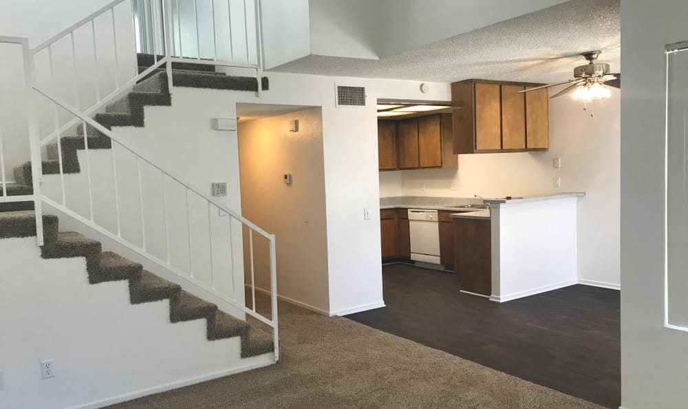 View of kitchen area and tiered stairway going upstairs in model home at Cordova Park Apartment Homes
