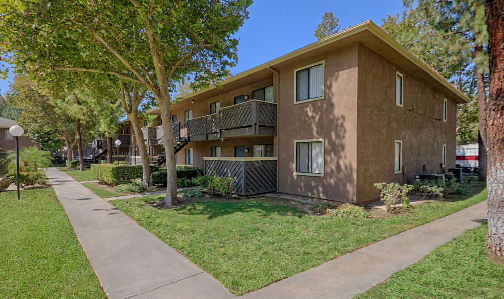 Exterior resident building showcasing well-maintained landscaping at Creekside Village Apartment Homes in San Bernardino, CA
