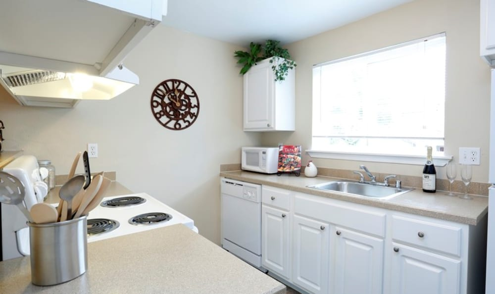 Bright kitchen with modern appliances in model home at Discovery Landing Apartment Homes in Burien, WA