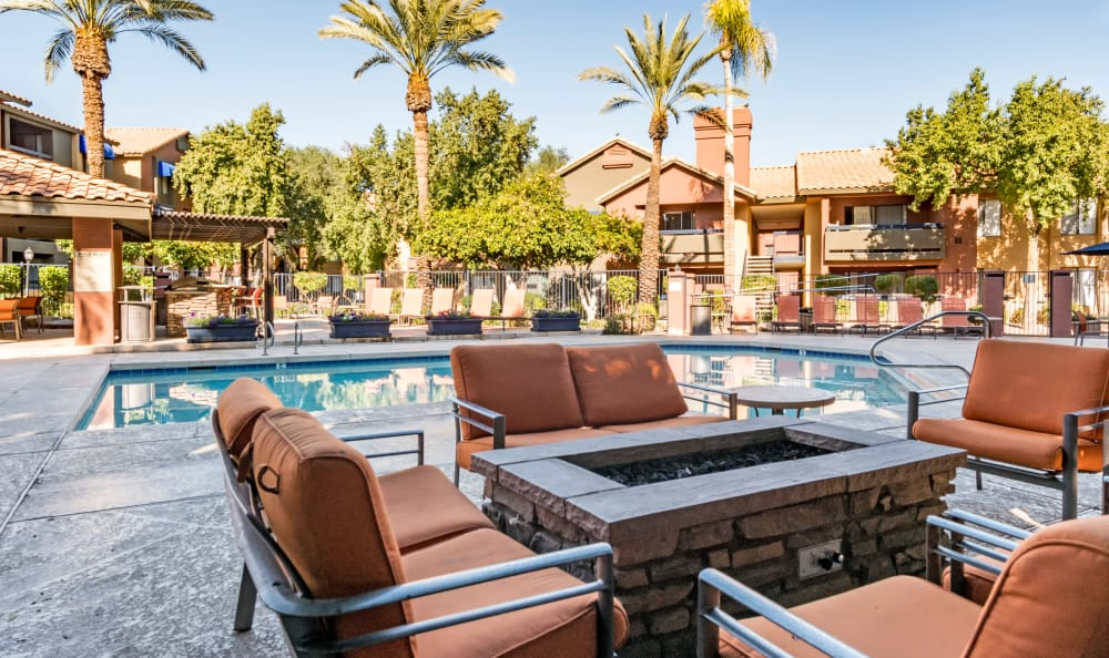 Seating by the fire pit and pool at Elliot's Crossing Apartment Homes in Tempe