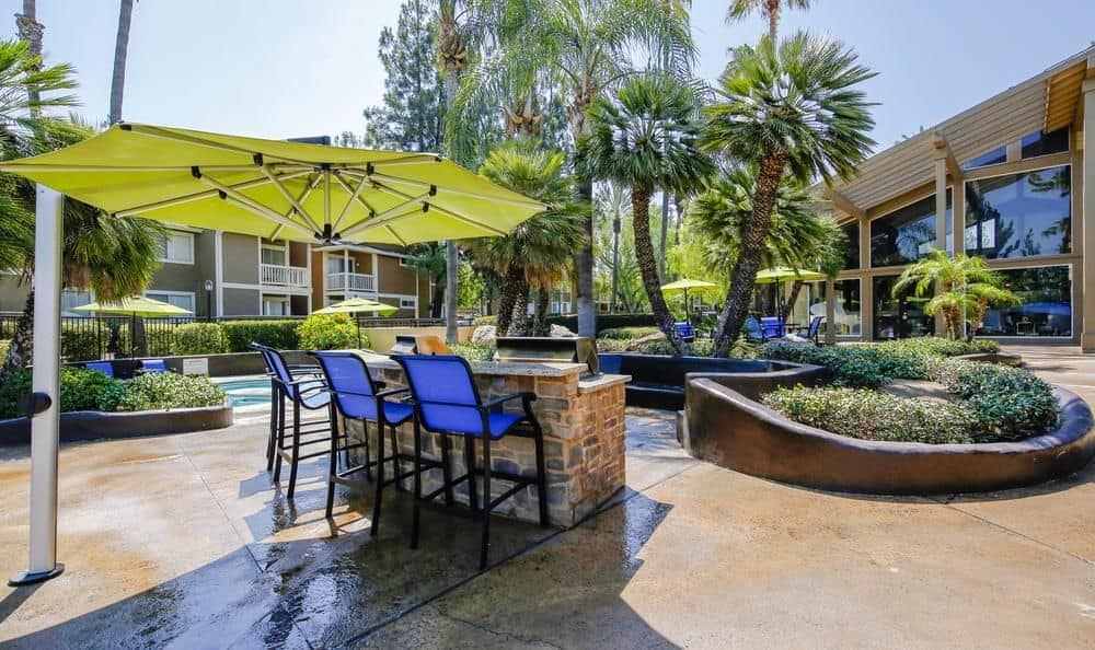 Table with umbrella near the swimming pool at Redlands Lawn and Tennis Club in Redlands