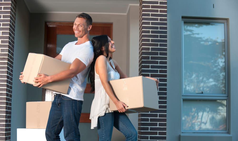 Couple carrying boxes to Hallmark Mini Storage