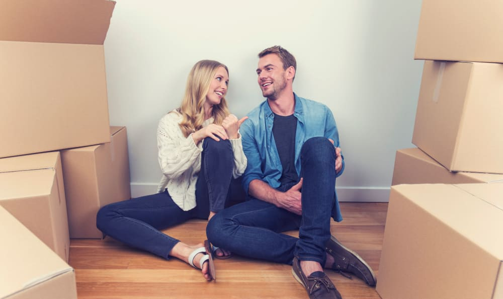 Couple on the floor surrounded by moving boxes near Hallmark Mini Storage