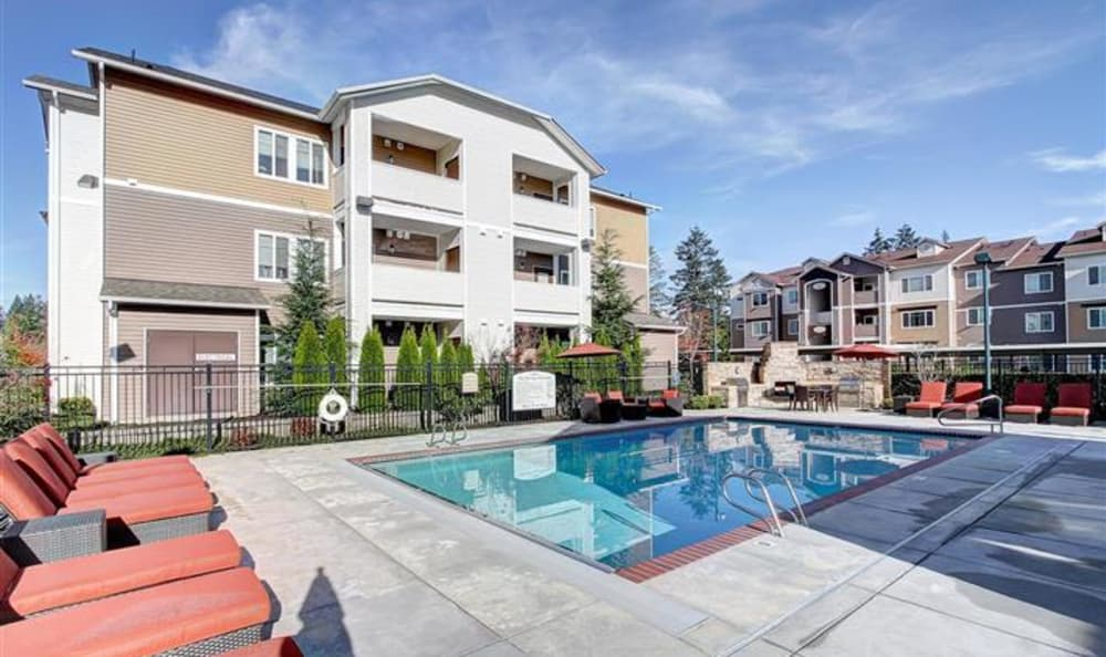 Gorgeous swimming pool area and plenty of seating nearby at Woodland Apartments in Olympia, WA