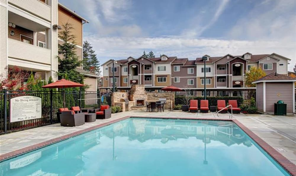 Swimming pool area at Woodland Apartments in Olympia, WA, on a beautiful day