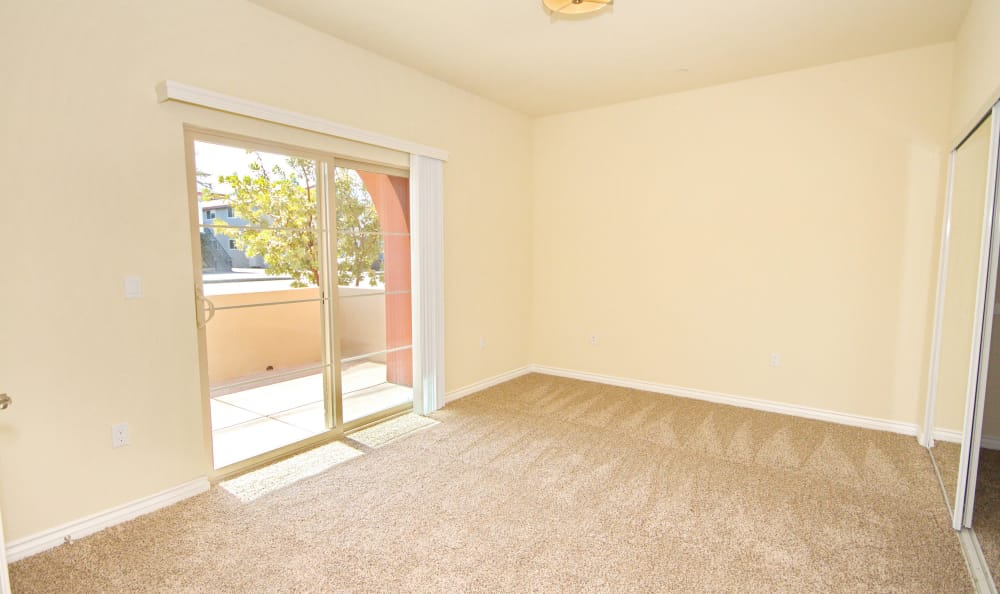 Empty spare bedroom with sliding door to private balcony in model home at IMT Townhomes at Magnolia Woods in Sherman Oaks, CA