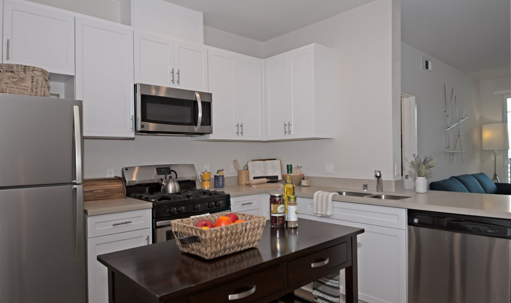 Island, granite countertops, and stainless appliances in model home kitchen at IMT Sherman Circle in Van Nuys, CA