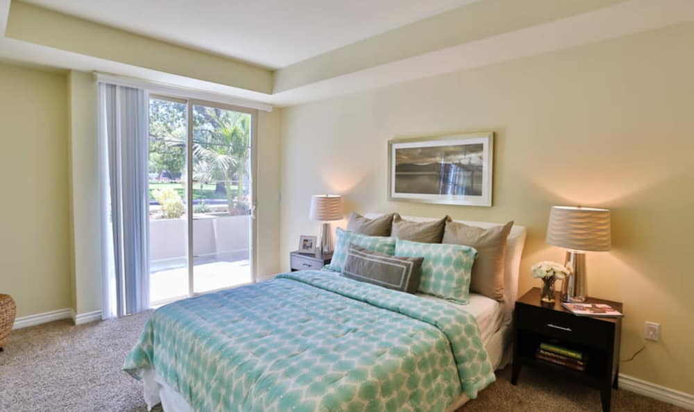 Model home's master bedroom with plush carpeting and a private balcony at IMT Park Encino in Encino, California