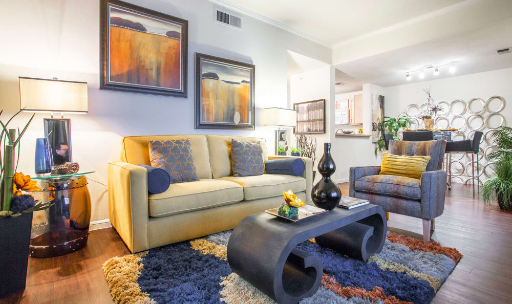Well-decorated living room with hardwood floors in model home at Riata in Austin, TX