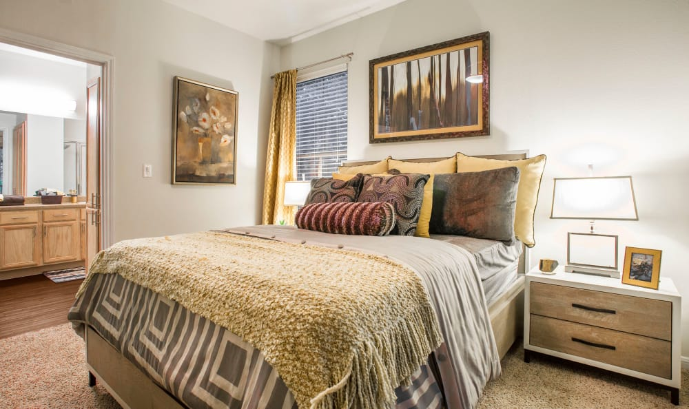Spacious and lavish master bedroom with ensuite bathroom in model home at Riata in Austin, TX