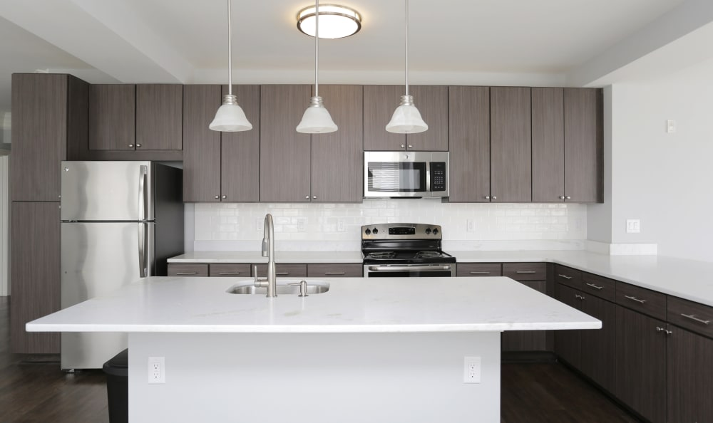 Gorgeous gourmet kitchen with subway-tile backsplash and dark wood cabinetry in model home at Aqua on 25th in Virginia Beach, VA