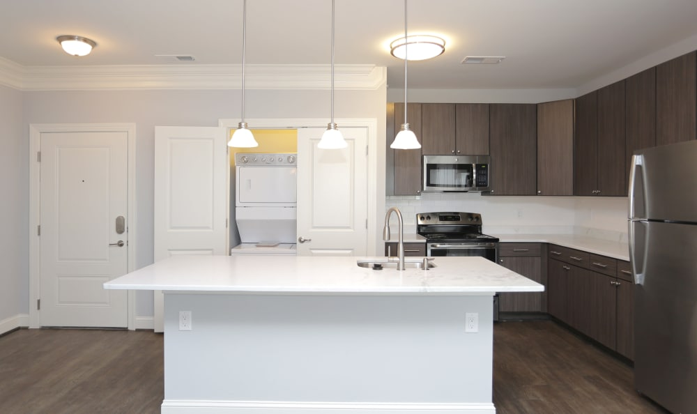 Modern kitchen with adjacent washer and dryer in model home at Aqua on 25th in Virginia Beach, VA