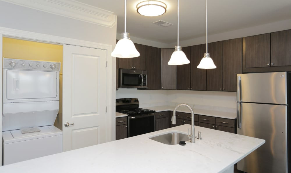 Dark wood cabinetry and stainless-steel appliances in model home's kitchen at Aqua on 25th in Virginia Beach, VA