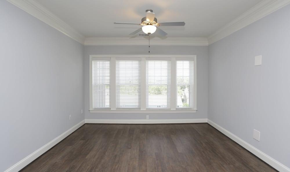 Hardwood floors, oversized windows, and ceiling fan in model home bedroom at Aqua on 25th in Virginia Beach, VA