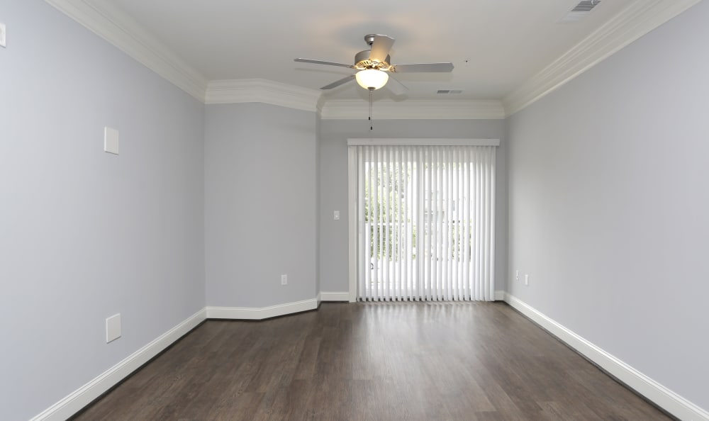 Spacious living room with hardwood floors and private balcony in model home at Aqua on 25th in Virginia Beach, VA