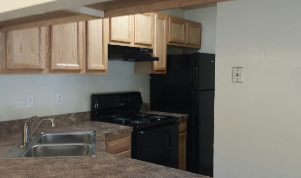 Black appliances in modern kitchen of model home at Woodbriar Apartments in Chesapeake, Virginia