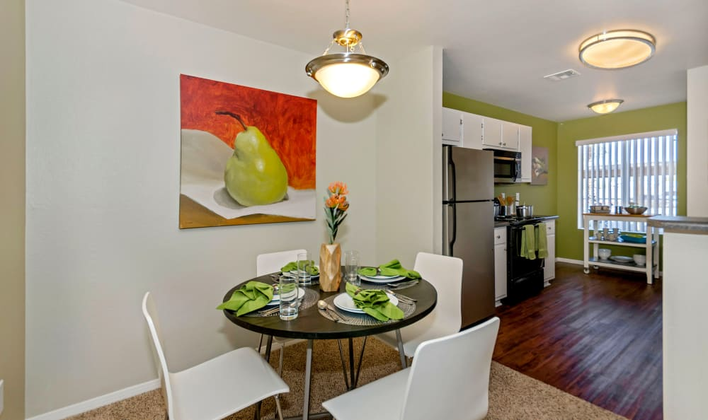 Dining area looking into kitchen with hardwood floor in model home at The Boulevard in Phoenix, Arizona