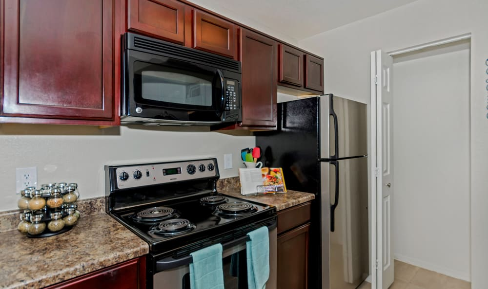 Dark wood cabinetry and stainless-steel appliances in the kitchen at The Boulevard in Phoenix, Arizona