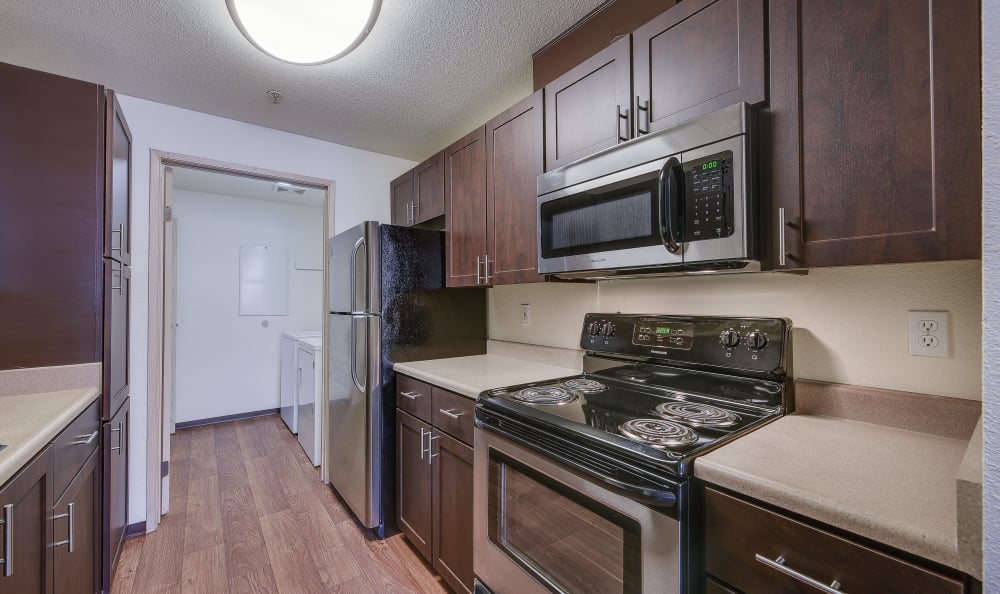 Brown renovation Kitchen with stainless steel appliances, view into in-home laundry at Renaissance at 29th Apartments