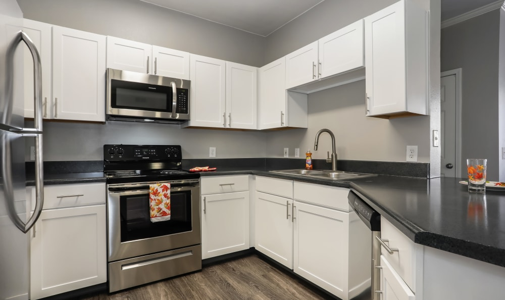 white renovation Kitchen with stainless steel appliances at Hawthorne Hill Apartments in Thornton